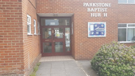 image shows the entrance to the church hall. It is step-free. To the right of the door is a noticeboard and a sign that says PARKSTONE BAPTIST CHURCH but both the letters C in CHURCH are missing