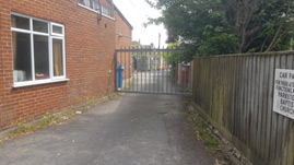 image shows the side entrance to the carpark to the right of the church hall off Loch Road. The gate is closed